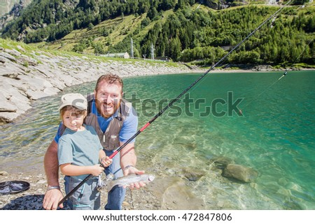 Dad and daughter fishing together a trout in a mountain lake