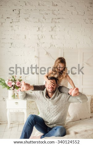 Dad and daughter playing and laughing in bed, happy family - stock photo