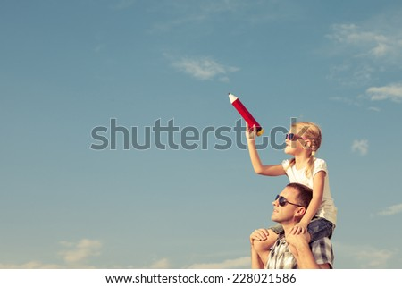 Dad and daughter playing near a house at the day time - stock photo