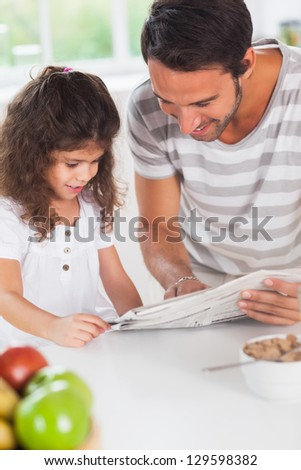 Dad and daughter reading a newspaper in kitchen - stock photo
