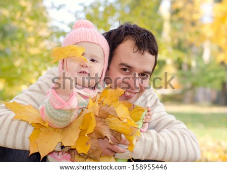 Dad and daughter with leaves in autumn park