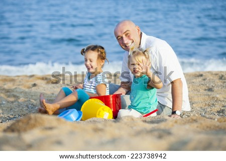 Dad and daughters playing on  beach.
