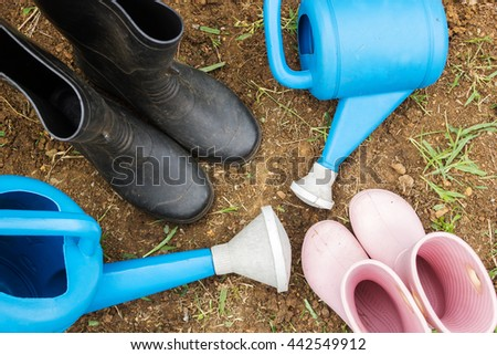 Dad and girl gardening boots in garden. Relationship and activity of family. Agriculture background. Top view. - stock photo