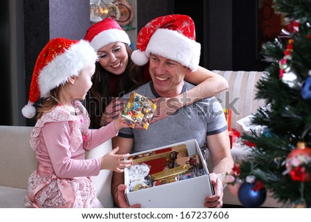 Dad and her small daughter decorate a christmas fur-tree