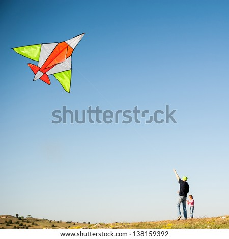 Dad and his little daughter flying a kite. Family Vacation - stock photo