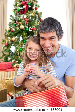 Dad and little girl playing with Christmas presents at home - stock photo