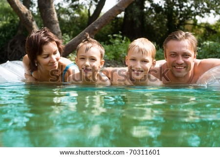 Dad and mom with two boy to the river - stock photo