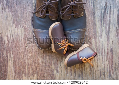 Dad and son brown shoes on rustic wooden background, father's day  - stock photo