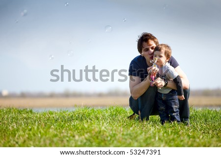 dad and son making soap bubbles in the nature - stock photo