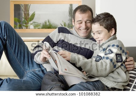 Dad and son reading a magazine while lounging on the living room's sofa.