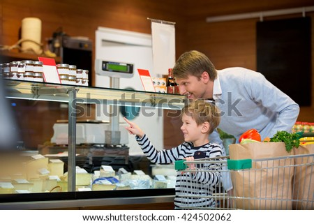Dad and son with cart at showcase - stock photo
