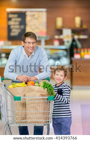 Dad and son with shopping cart - stock photo
