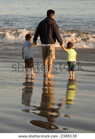 Dad and two Children Playing at the Ocean Edge - stock photo