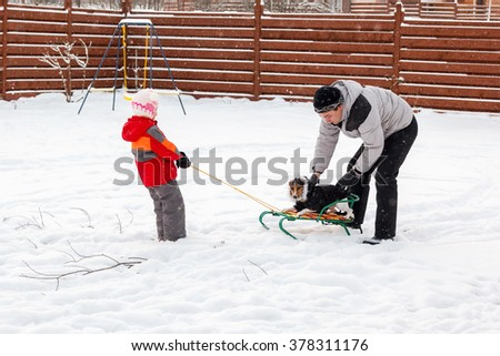 Dad daughter and dog sledding in the backyard - stock photo
