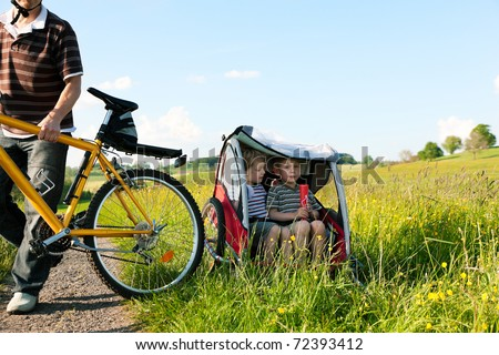 Dad driving his two children on a weekend excursion with bikes on a summer day in beautiful landscape, for safety and protection they are sitting in a bike trailer - stock photo
