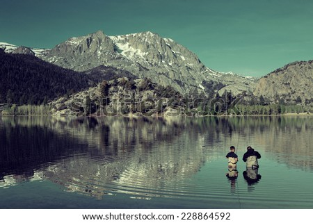 Dad fishing with son in lake in Yosemite.