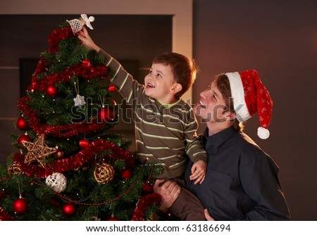 Dad helping son to decorate christmas tree, boy putting up the top ornament, smiling. - stock photo