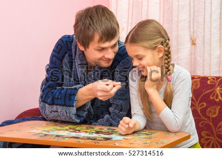 Dad holds daughter fun puzzle element