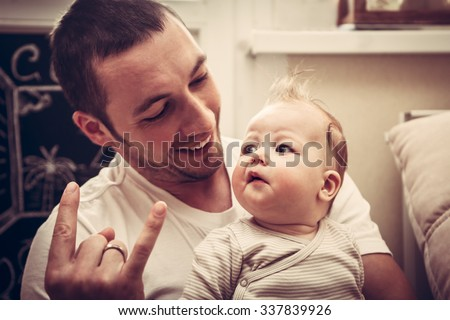Dad introduces his little baby daughter with modern youth music culture - stock photo