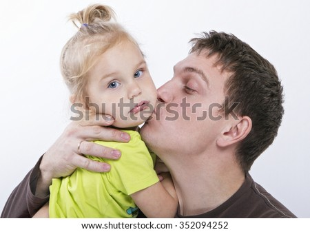 Dad kissing her pretty daughter, with beautiful eyes and blonde hair. There is concept of father's love and care for their children - stock photo