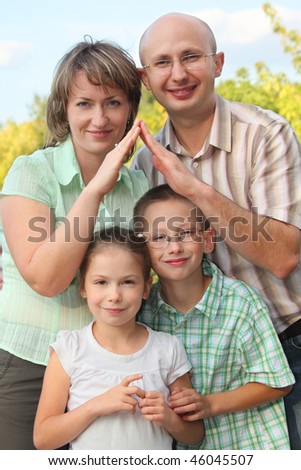 dad, mom, little boy and girl in early fall park. dad and mom  is using their hands to represent home. focus on son's face. - stock photo