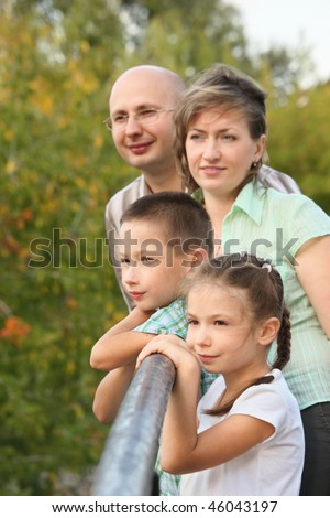 dad, mom, little boy and girl is lean elbow on bridge fence and looking away - stock photo
