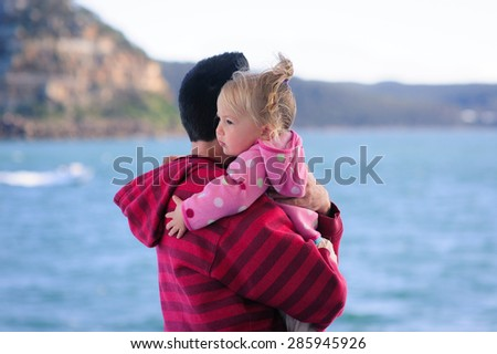 Dad or father and his baby daughter hugging on a boat or ferry in the sea on a cool summer day - stock photo