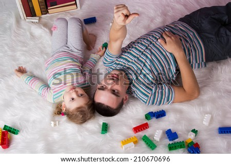 Dad playing with child at home, tells and shows his hand up - stock photo