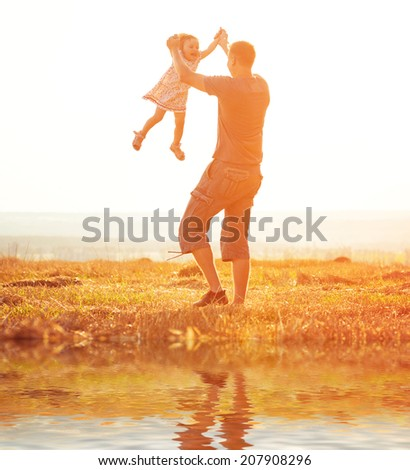 Dad playing with his aughter in a field at sunset - stock photo