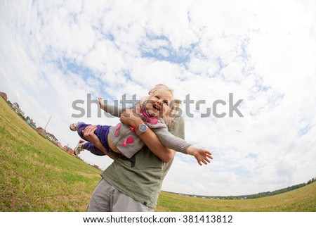 Dad playing with his baby daughter, he turns her around himself, selective focus, the effect of motion and fisheye (perspective) - stock photo