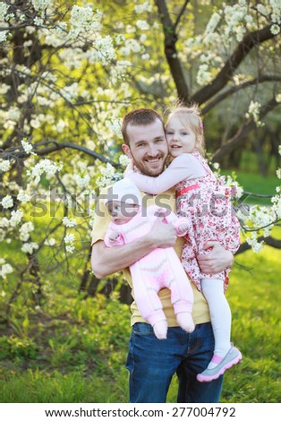 Dad playing with his daughters, he holds them in his arms. Selective focus - stock photo