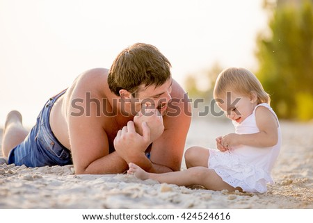 Dad playing with his little daughter at the beach in summer. Man lying on the sand near his little daughter on the beach and smiling. A girl in a white dress. - stock photo