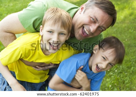Dad plays with young children outdoors