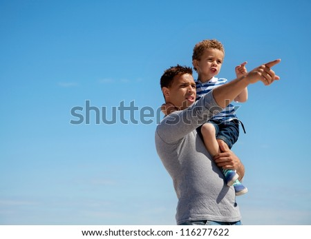 Dad pointing something to his little son outdoors - stock photo