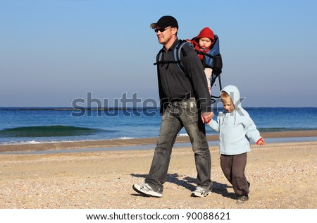 Dad, son and daughter during a walk along the sea - stock photo