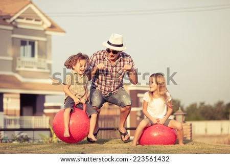 Dad, son and daughter jumping on inflatable balls on the lawn in front of house at the day time - stock photo