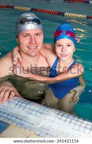 Dad teaching his daughter to swim in the pool - stock photo
