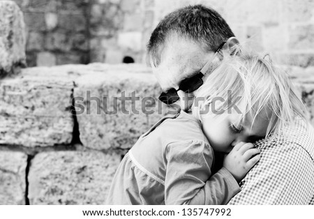 Dad with a sleeping baby in his arms - stock photo