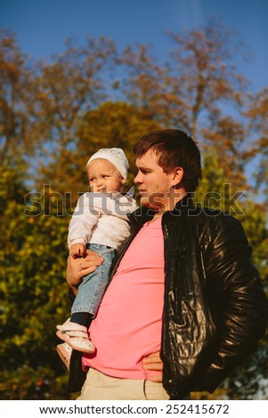 Dad with his daughter in his arms in the park