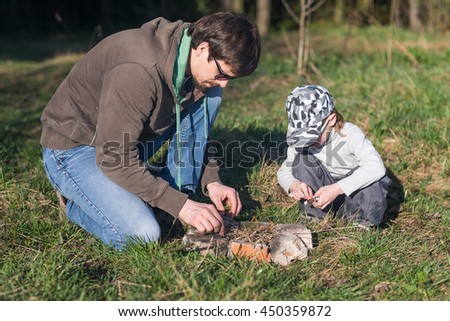 Dad with son kindle bonfire on a picnic in the woods. The concept of parenting, fatherhood. - stock photo