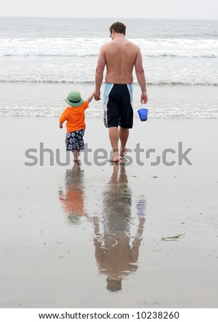 dad with toddler son on beach - stock photo