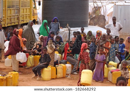 DADAAB, SOMALIA - AUGUST 07: Refugee camp, hundreds of thousands of difficult conditions, Somali immigrants are staying. African people waiting to get in the water. August 07, 2011 in Dadaab, Somalia. - stock photo