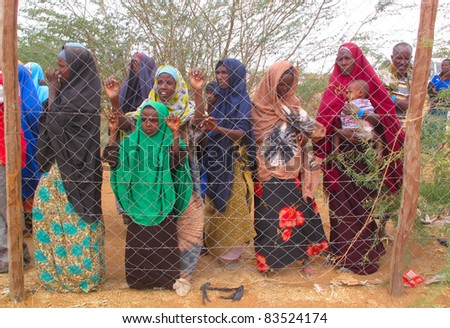 DADAAB, SOMALIA-AUGUST 15: Unidentified women and children wait for relief aid in the Dadaab refugee camp where thousands of Somalis end up due to hunger on August 15, 2011 in Dadaab, Somalia. - stock photo