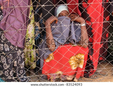 DADAAB, SOMALIA-AUGUST 15: Unidentified women waits behind a fence for relief aid in the Dadaab refugee camp where thousands of Somalis end up due to hunger on August 15, 2011 in Dadaab, Somalia. - stock photo