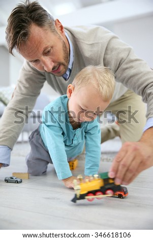 Daddy and baby boy playing with toys on the floor - stock photo