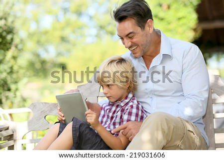 Daddy and son playing with tablet outside - stock photo