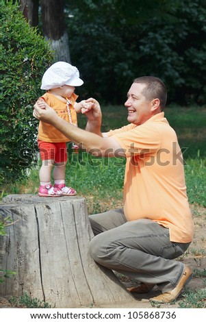 Daddy holds little cute daughter by the hand, standing on a stump in the park