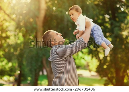 Daddy playing active games with his son outside. Happy family portrait. Laughing dad with little boy enjoying nature together. Joyful family. Free, freedom concept. Summer holidays, vacation. - stock photo
