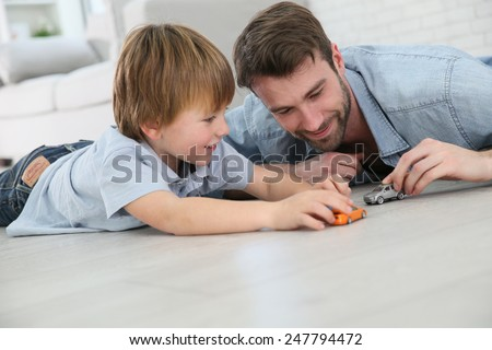 Daddy with little boy playing with toy cars - stock photo
