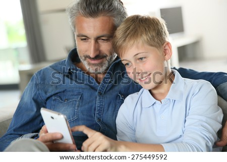 Daddy with son playing with smartphone - stock photo